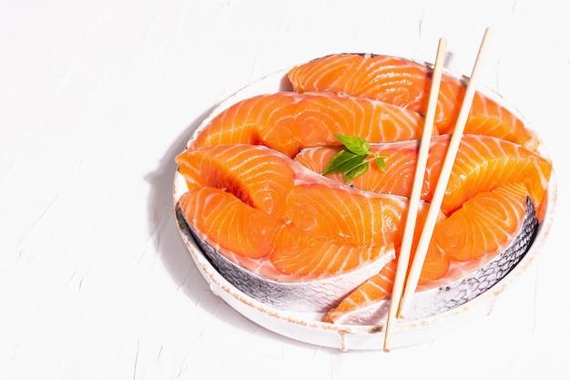 Bifes de filé de peixe fresco cru de salmão ou truta. design minimalista, luz dura moderna, sombra escura. ingredientes refrigerados para cozinhar frutos do mar saudáveis. fundo culinário de massa branca, copie o espaço