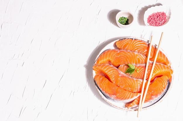 Bifes de filé de peixe fresco cru de salmão ou truta. design minimalista, luz dura moderna, sombra escura. ingredientes refrigerados para cozinhar frutos do mar saudáveis. fundo culinário de massa branca, vista superior