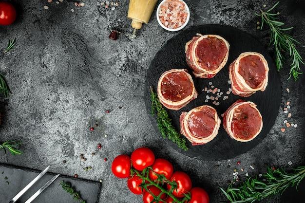 Bifes de filé mignon alimentados orgânicos crus envoltos em bacon servido no fundo escuro de concreto, pedaços de carne de porco prontos para cozinhar, banner, lugar de receita de menu para texto, vista de cima.
