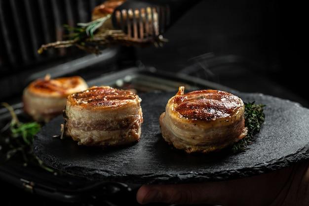 Bifes de medalhões do filé mignon coberto de bacon na grelha com fundo escuro de fumaça. cozinhar bife na grelha pelas mãos do chef.