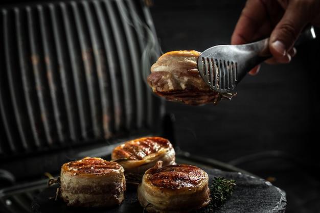 Bifes de medalhões do filé mignon coberto de bacon na grelha fundo escuro. cozinhar bife na grelha pelas mãos do chef.