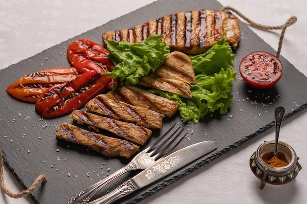 Bifes de peito de peru grelhados caseiros com pimentão assado e tomate em um quadro negro com