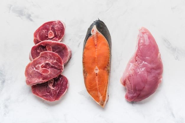 Bifes de peixe, filé de frango e bifes de peru em uma superfície clara
