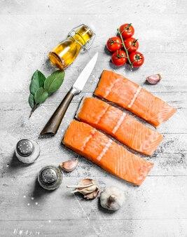 Bifes de peixe salmão cru com especiarias. sobre uma mesa rústica.