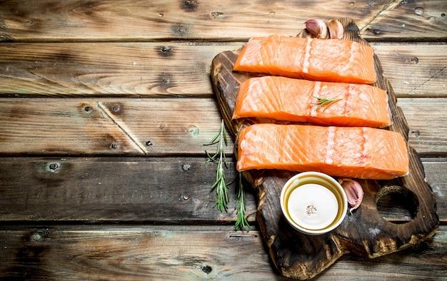 Bifes de peixe salmão cru em uma placa de corte com alecrim e azeite na mesa de madeira.