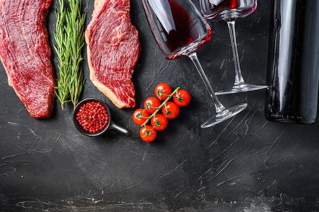 Bifes de picanha crus perto da garrafa e do copo de vinho tinto, sobre a vista superior da mesa texturizada preta com espaço para texto.