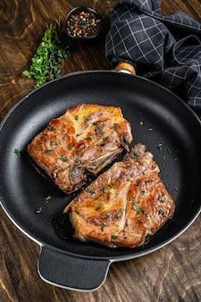 Bifes de porco assados na frigideira de carne do pescoço. fundo de madeira escuro. vista do topo.