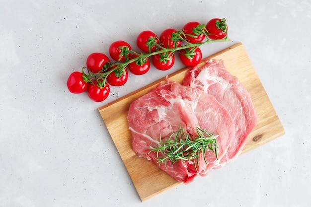 Bifes de porco cru deitado sobre uma tábua de madeira com um raminho de alecrim e tomate cereja vermelho