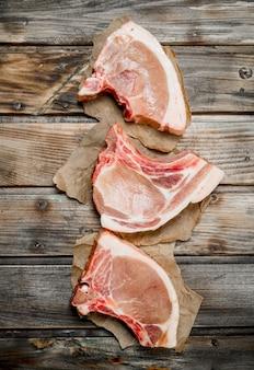 Bifes de porco crus com osso. em uma madeira.