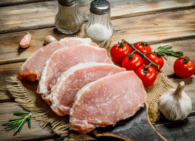 Bifes de porco crus com tomate e alecrim. em uma madeira.