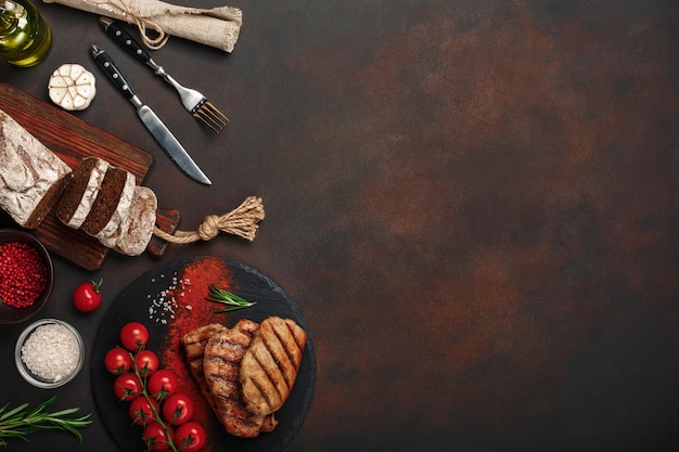 Bifes de porco grelhado com garrafa de vinho, copo de vinho, faca, garfo, pão preto, tomate cereja e alecrim