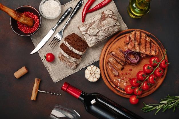 Bifes de porco grelhado fatiado com garrafa de vinho, copo de vinho, saca-rolhas, faca, garfo, pão preto, tomate cereja, alho