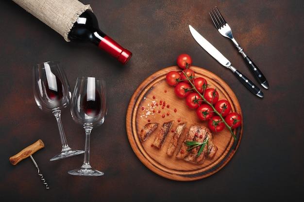 Bifes de porco grelhado fatiado com garrafa de vinho, copo de vinho, saca-rolhas, faca, garfo, pão preto, tomate cereja