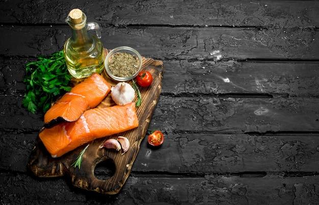 Bifes de salmão cru com ervas e especiarias na mesa rústica preta.