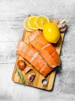 Bifes de salmão cru com especiarias e rodelas de limão. em um rústico
