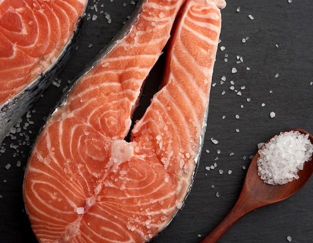 Bifes de salmão cru com sal branco sobre preto