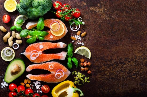 Bifes de salmão cru, ervas aromáticas, cebola, limão, sal e legumes frescos para cozinhar