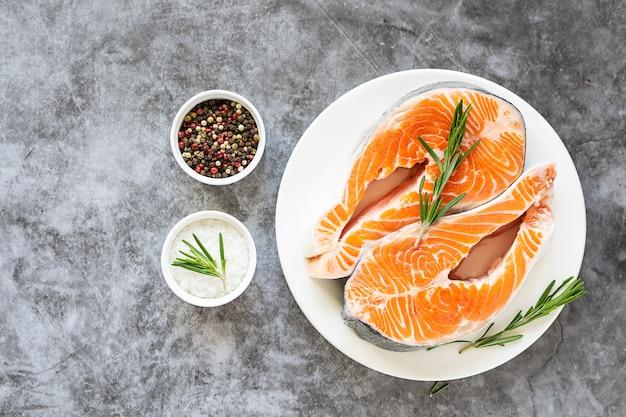 Bifes de salmão crus com alecrim e especiarias na mesa de mármore escura.
