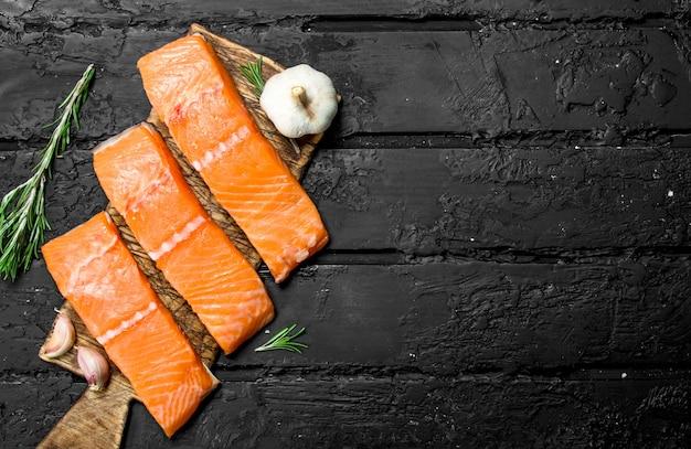 Bifes de salmão crus com alho e alecrim. em preto rústico.