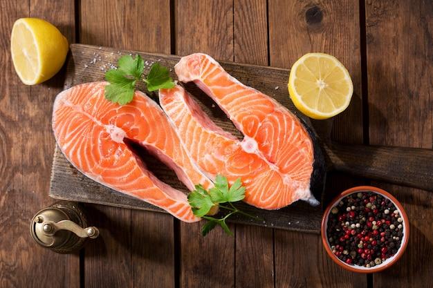 Bifes de salmão fresco com ingredientes para cozinhar em uma mesa de madeira, vista superior