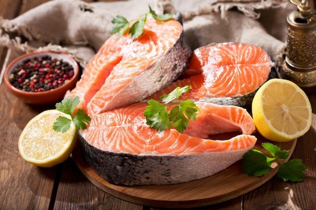 Bifes de salmão fresco com ingredientes para cozinhar em uma mesa de madeira
