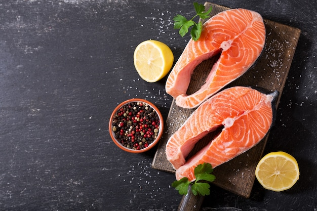 Bifes de salmão fresco com ingredientes para cozinhar em uma tábua de madeira, vista de cima