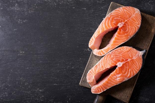 Bifes de salmão fresco em tábua de madeira, vista de cima