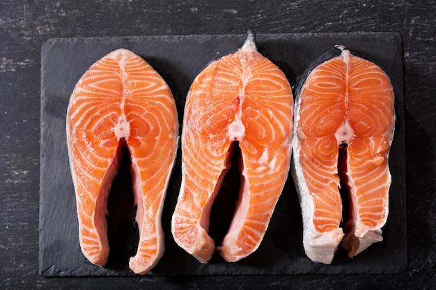 Bifes de salmão fresco no quadro escuro, vista de cima