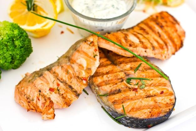 Bifes de salmão grelhado. servido com legumes e especiarias em um prato branco