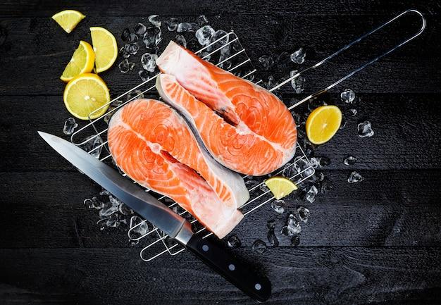 Bifes de salmão no gelo na vista superior de mesa de madeira