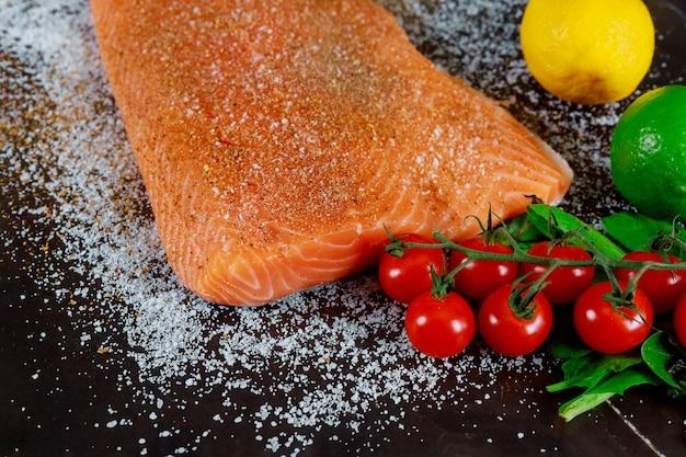 Bifes de salmão no tabuleiro escuro marinado com ervas e especiarias