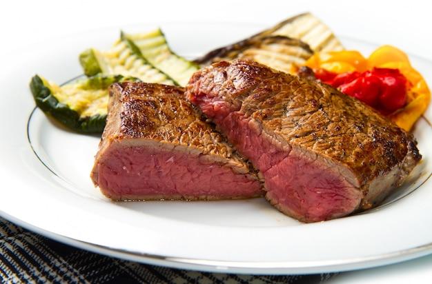Bifes deliciosos no prato branco com legumes grelhados