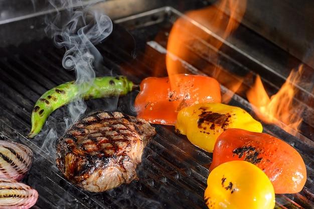Bifes e legumes na grelha com chamas