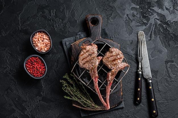 Bifes grelhados de carne de carneiro de cordeiro na grelha. fundo preto. vista do topo.