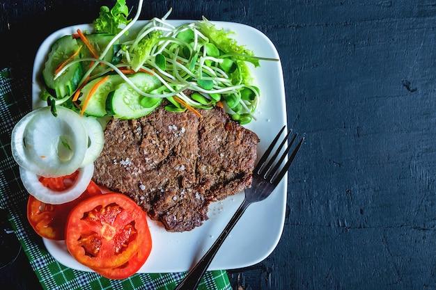 Bifes grelhados e saladas saudáveis em cima da mesa