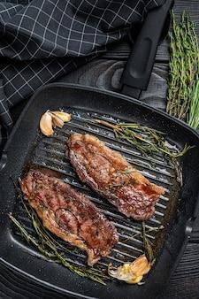 Bifes grelhados prime black angus striploin ou new york em uma assadeira. fundo de madeira escuro. vista do topo.