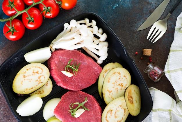 Bifes suculentos crus em uma panela pronta para assar no concreto rústico. bifes de carne fresca com ervas, alho, pimenta, sal e tomate.