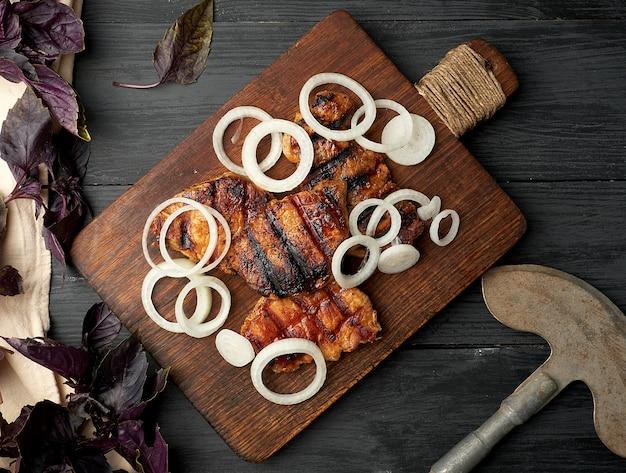 Bifes suculentos de carne de porco grelhada em uma placa de madeira marrom