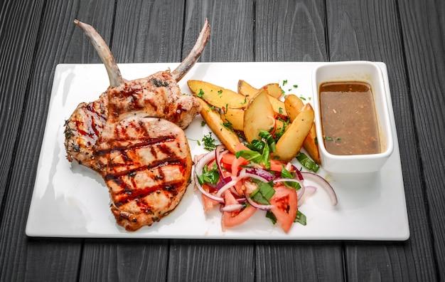 Bifes tomahawk grelhados na hora, com batatas fritas, legumes e molho