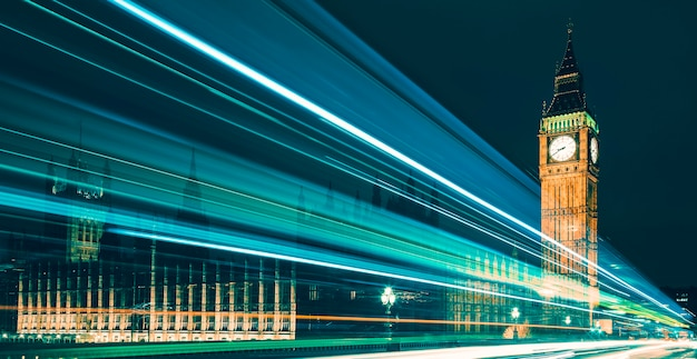 Big ben, um dos símbolos mais proeminentes de londres e inglaterra, mostrado à noite junto com as luzes dos carros que passam