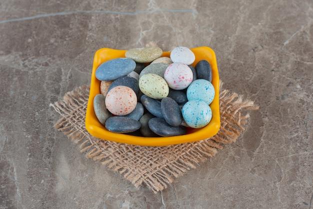 Bight bombons de pedra multicoloridos em uma tigela laranja.