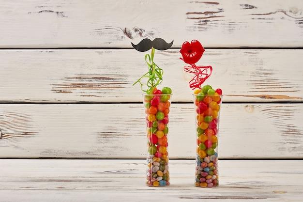 Bigode de apoio e lábios. vasos cheios de pedras de doce. presente criativo e colorido.
