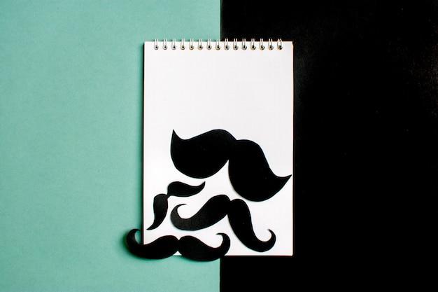 Bigode de papel preto, bloco de notas em fundo azul mês doações controle de cânula de próstata