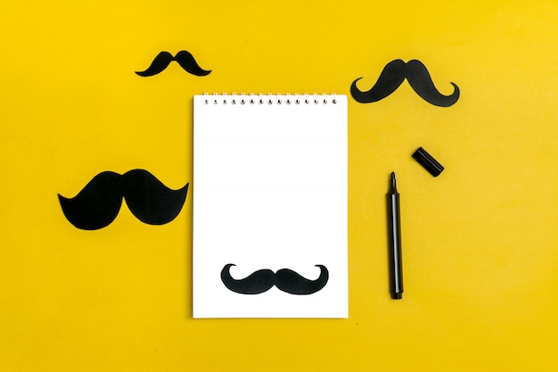 Bigode de papel preto, bloco de notas, lápis sobre fundo azul mês doações controle de prosta
