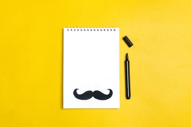 Bigode de papel preto, chapéu, óculos, bloco de notas sobre fundo amarelo doações de mês, conceito de dia dos pais