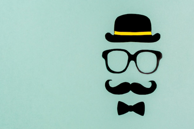 Bigode de papel preto, chapéu, óculos em fundo azul controle de doações mensais de próstata