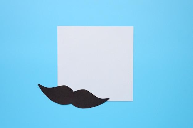 Bigode de papel preto e etiqueta do papel de escrita sobre um fundo azul. conceito de conscientização da saúde dos homens e câncer de próstata. movember. espaço para texto
