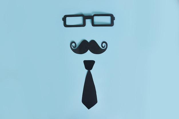 Bigode decorativo homem, óculos escuros e gravata borboleta em uma madeira azul clara