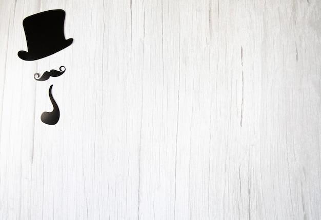 Bigode falso, laço de gravata e chapéu em um fundo branco de madeira.