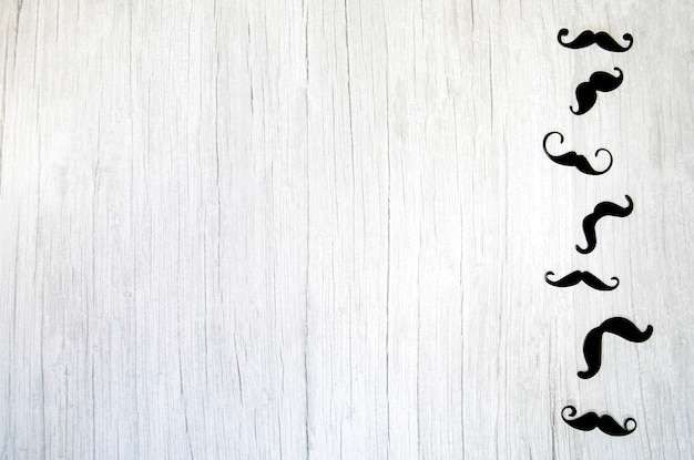 Bigode falso, laço de gravata e chapéu em um fundo de madeira branco. conceito de dia internacional dos homens e dia dos pais plano leigo, vista de cima, cópia espaço para texto